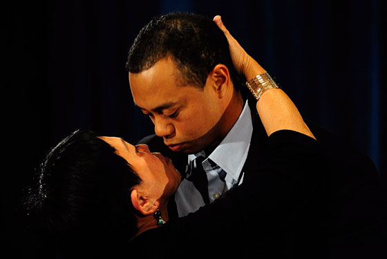 Tiger kisses his mother at today's press conference.