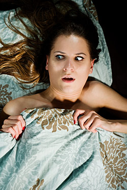 In the original version of this stock image, the woman pictured is reacting to finding a male sex doll in bed with her. No joke.