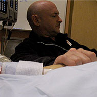 Husband Mark Kelly sits next to Gabby's hospital bed.